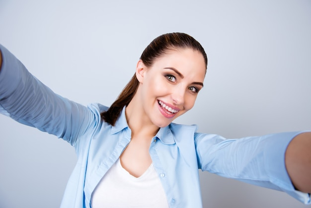 Całkiem pozytywna wesoła młoda kobieta dokonywanie selfie na białym tle szarej przestrzeni