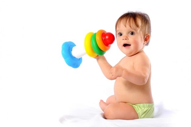Całkiem rok małe dziecko bawi się kolorową piramidą.