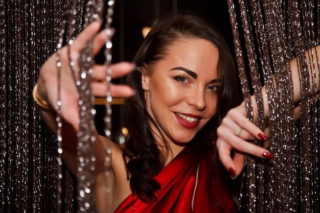 Całkiem seksowna czarująca brunetka w czerwonej sukience koktajlowej wygląda zza zasłony ze srebrnych nici. emocja kobiecego flirtu i aktorki. koncepcja zabawy i flirtu. skopiuj miejsce