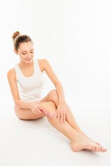 Całkiem seksowna młoda kobieta goli nogę na białym tle