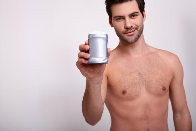 Całkiem seksowny mężczyzna trzyma w ręku szary dezodorant