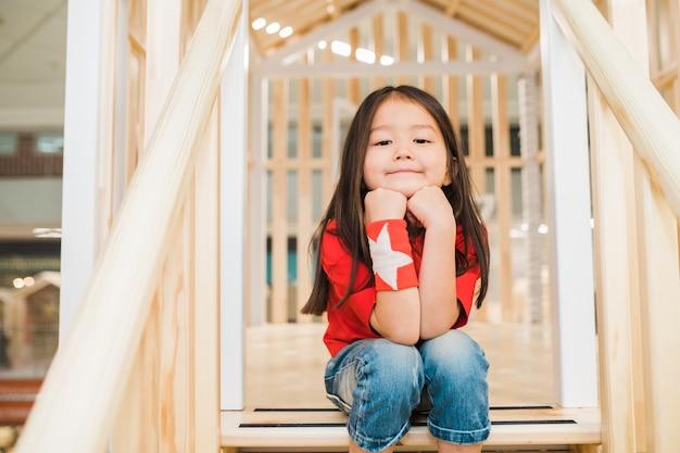 Całkiem spokojna dziewczynka w dżinsach i czerwonej koszulce siedzi na drewnianych schodach na placu zabaw między poręczami