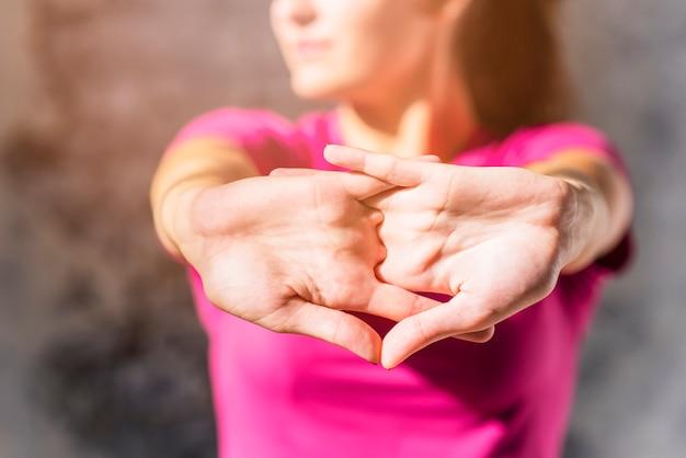 Całkiem sportowy młoda kobieta rozciąganie spinające ręce
