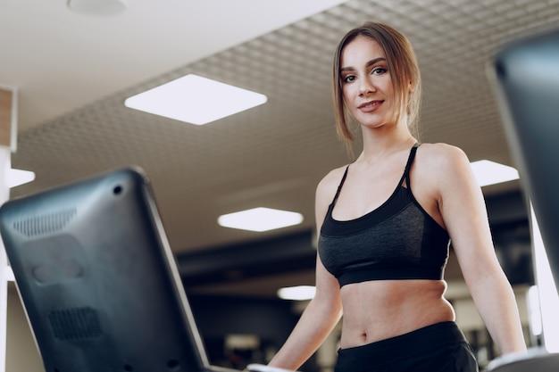 Całkiem sprawna kobieta w czarnym sportrswear szkolenia na bieżni
