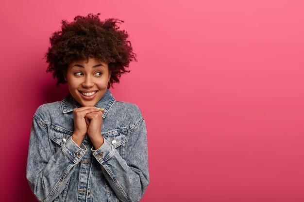 Całkiem szczęśliwa afro amerykanka uśmiecha się pozytywnie, trzyma ręce pod brodą