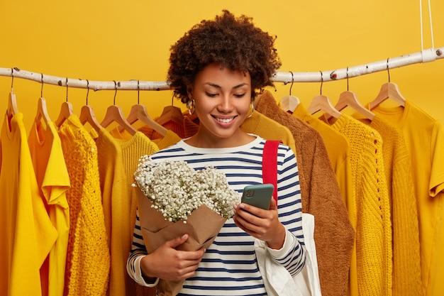 Całkiem szczęśliwa afro kobieta skupiona na smartfonie, trzyma piękny bukiet, uśmiecha się radośnie, stoi przy żółtych ubraniach wiszących na wieszakach.