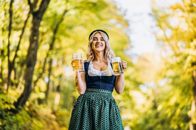 Całkiem szczęśliwa blondynka w dirndl, tradycyjny strój festiwalowy, trzymająca dwa kufle piwa na zewnątrz w lesie