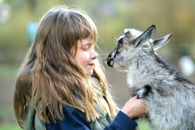 Całkiem szczęśliwa dziecko dziewczyna bawić się z małym koźlęciem na podwórku gospodarstwa.