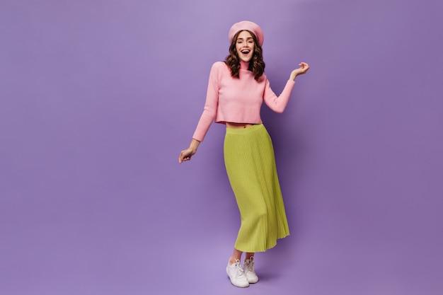 Całkiem szczęśliwa kędzierzawa kobieta tańczy na fioletowej ścianie