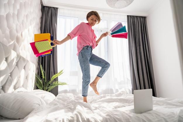 Całkiem szczęśliwa kobieta bawi się skacząc na łóżku w domu z kolorowymi torbami na zakupy