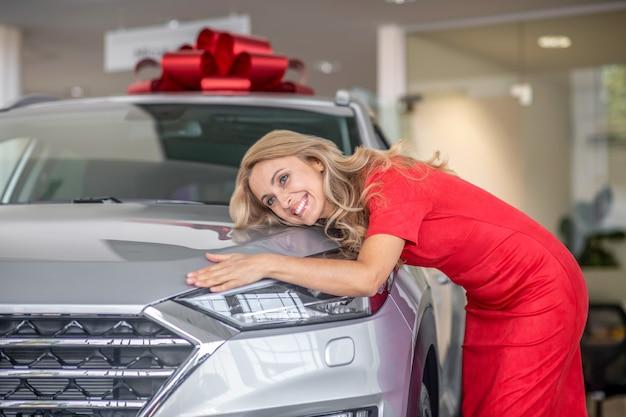 Całkiem szczęśliwa kobieta dotykająca podarowanego samochodu