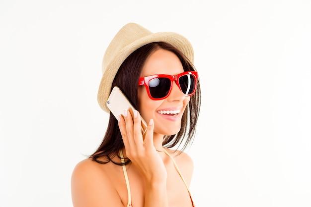 Całkiem szczęśliwa kobieta rozmawia przez telefon komórkowy w letni kapelusz i okulary