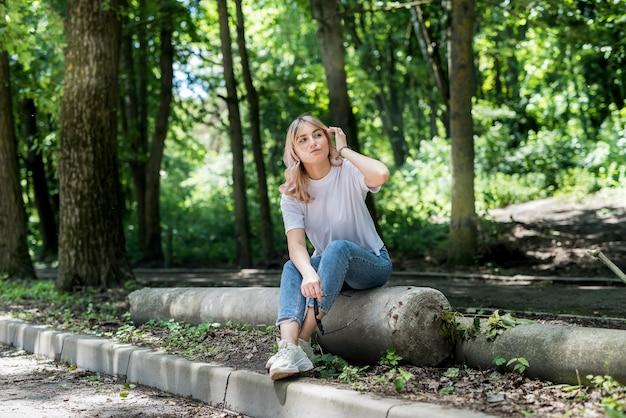 Całkiem szczęśliwa kobieta spędza czas w zielonym parku