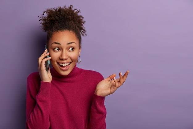 Całkiem szczęśliwa kobieta z zaskoczonym pozytywnym wyrazem twarzy prowadzi przyjazną rozmowę