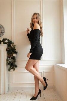 Całkiem szczęśliwa młoda stylowa kobieta w modnej czarnej sukience z seksownymi nogami i butami stoi w pobliżu białej ściany w pomieszczeniu