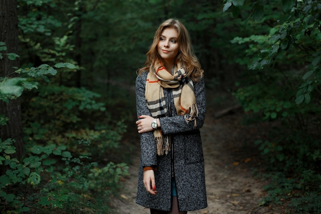 Całkiem szczęśliwa piękna europejska młoda kobieta w szaliku w kratkę vintage w modnym szarym płaszczu spaceruje po lesie w pobliżu zielonych krzewów