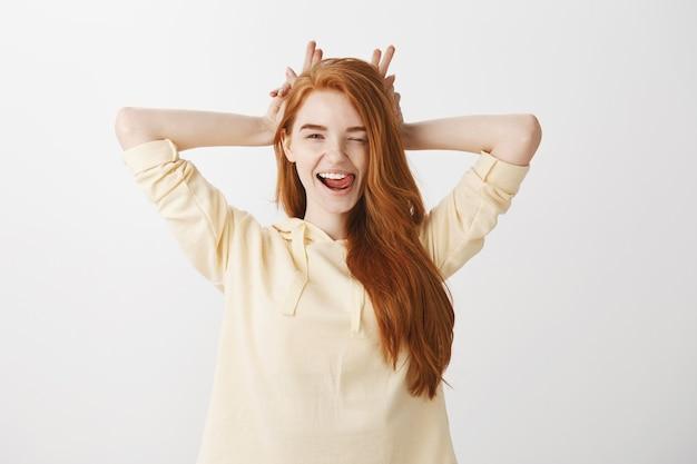 Całkiem szczęśliwa ruda kobieta uśmiecha się i pokazuje śmieszne uszy królika nad głową
