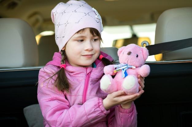 Całkiem szczęśliwe dziecko dziewczynka bawi się różowym misiem zabawka siedzi w bagażniku samochodu.