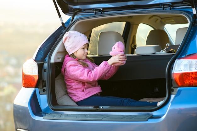 Całkiem szczęśliwe dziecko dziewczynka bawi się różowym misiem zabawki w bagażniku samochodu.
