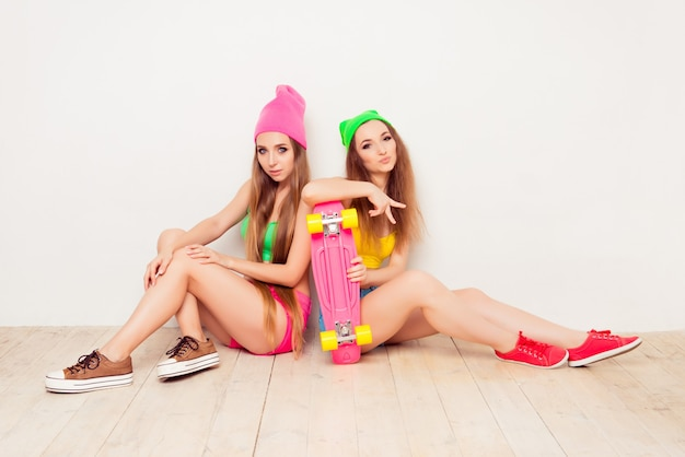 Całkiem szczęśliwe siostry w kolorowych ciuchach z skate