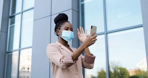Całkiem szczęśliwy african american młoda kobieta w masce medycznej o czacie wideo na smartfonie na zewnątrz budynku biznesowego. wesoła piękna kobieta rozmawia i prowadzi wideoczat przez kamerę internetową w telefonie komórkowym.