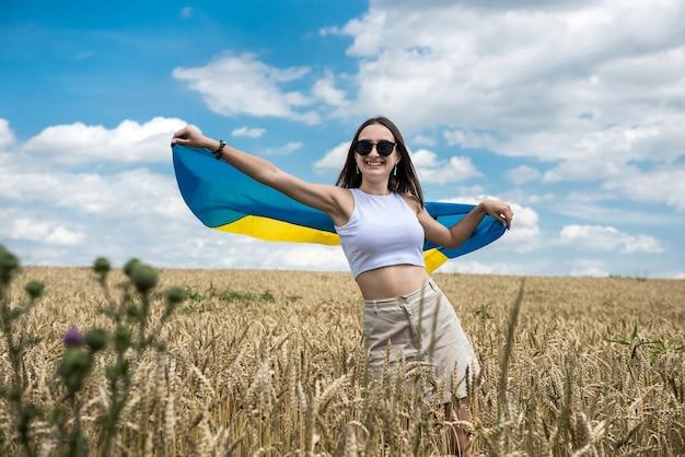 Całkiem szczupła dziewczyna z żółto-niebieską flagą ukrainy w polu pszenicy. styl życia