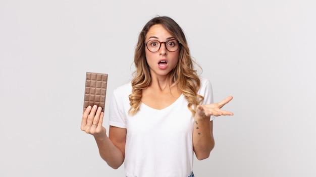 Całkiem szczupła kobieta czuje się bardzo zszokowana i zaskoczona i trzyma tabliczkę czekolady