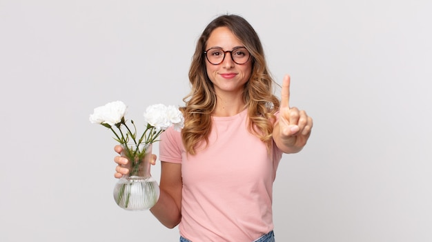 Całkiem szczupła kobieta, która uśmiecha się dumnie i pewnie robi numer jeden i trzyma ozdobne kwiaty
