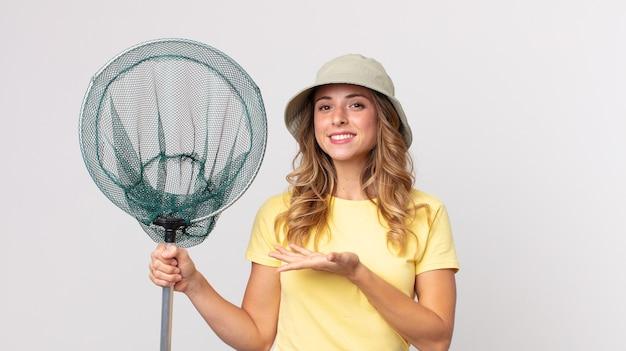 Całkiem szczupła kobieta uśmiecha się radośnie, czuje się szczęśliwa i pokazuje koncepcję w kapeluszu i trzyma siatkę na ryby