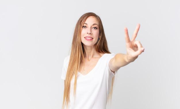 Całkiem szczupła kobieta uśmiechnięta i wyglądająca na szczęśliwą, beztroską i pozytywną, gestykulującą zwycięstwo lub pokój jedną ręką