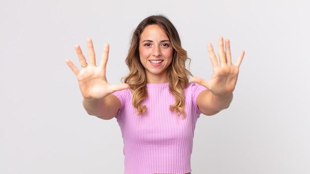 Całkiem szczupła kobieta uśmiechnięta i wyglądająca przyjaźnie, pokazująca cyfrę dziesiątą lub dziesiątą z ręką do przodu, odliczając w dół