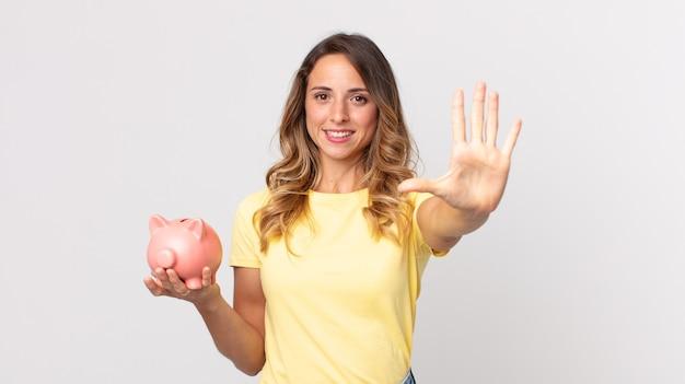 Całkiem Szczupła Kobieta Uśmiechnięta I Wyglądająca Przyjaźnie, Pokazująca Numer Pięć I Trzymająca Skarbonkę Premium Zdjęcia