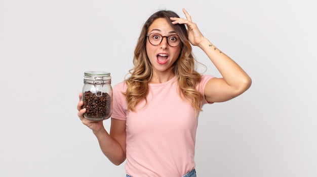 Całkiem szczupła kobieta wygląda na szczęśliwą, zdziwioną i zaskoczoną, trzymając butelkę ziaren kawy