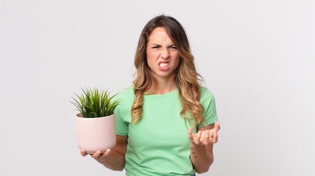 Całkiem szczupła kobieta wyglądająca na złą, zirytowaną i sfrustrowaną, trzymająca roślinę ozdobną