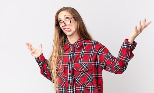 Całkiem szczupła kobieta wzruszająca ramionami z głupim, szalonym, zdezorientowanym, zdziwionym wyrazem twarzy, zirytowana i bezradna