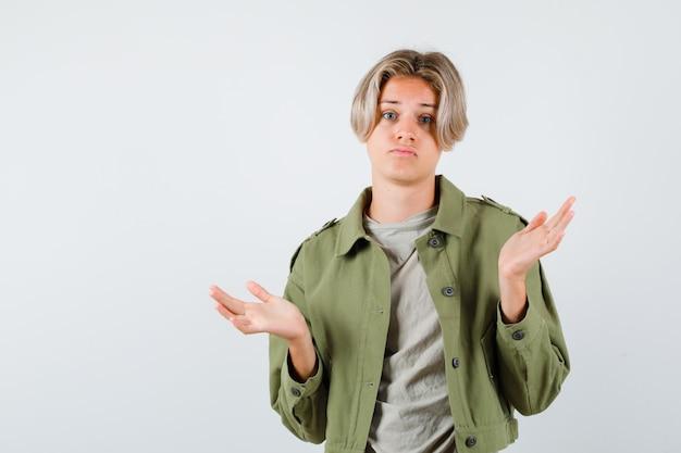 Całkiem teen chłopiec pokazując bezradny gest w zielonej kurtce i ponury. przedni widok.