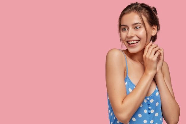 Całkiem urocza młoda dziewczyna ma czarujący uśmiech trzyma ręce razem