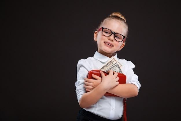 Całkiem urocza młoda dziewczyna w białej koszuli i czarnych spodniach trzyma czerwoną torebkę z pieniędzmi
