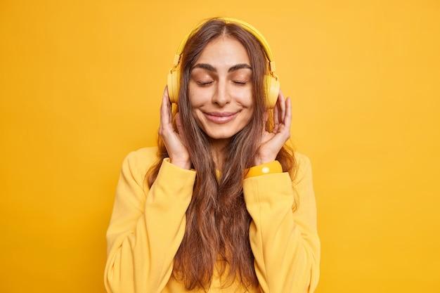 Całkiem urocza młoda kobieta cieszy się spokojną atmosferą, słucha muzyki przez słuchawki, ma zamknięte oczy