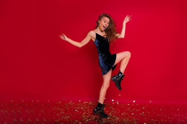 Całkiem urocza młoda kobieta tańczy na czerwonej ścianie w zimowym stroju