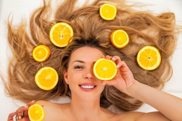 Całkiem uroczy radosny atrakcyjny wesoły pozytywny młoda kobieta z długimi włosami o kawałki pomarańczy, zamknij jedno oko na białym tle. pojęcie piękna, zdrowia i osobistej pielęgnacji ciała. skopiuj miejsce