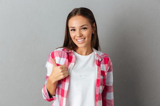 Całkiem uśmiechnięta brunetka dziewczyna w kraciaste koszule, pokazując kciuk do góry gest