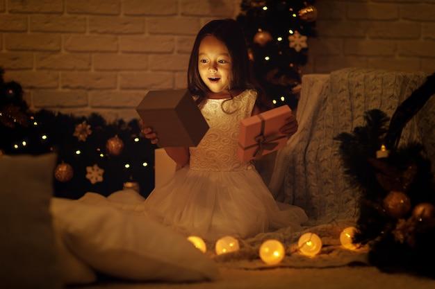 Całkiem uśmiechnięta dziewczyna otwierająca magiczne pudełko z prezentem świątecznym w domu