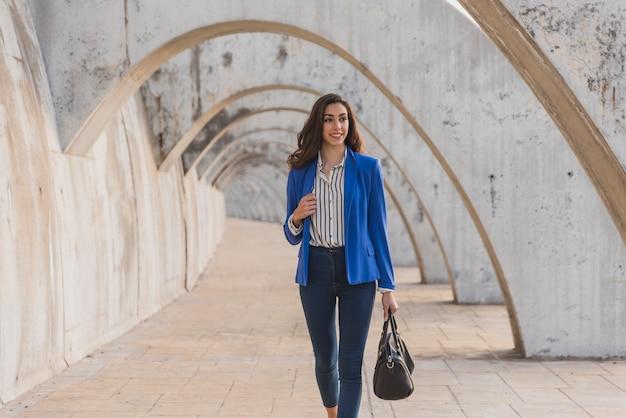 Całkiem uśmiechnięta dziewczyna trzyma torebkę i spacery
