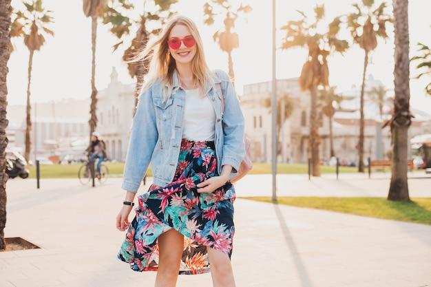 Całkiem uśmiechnięta, flirtująca romantyczna kobieta spacerująca po miejskiej ulicy w stylowej drukowanej spódnicy i dżinsowej kurtce oversize w różowych okularach przeciwsłonecznych