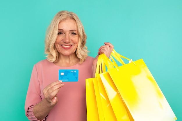 Całkiem uśmiechnięta kobieta shopacholic z kartą kredytową i torby na zakupy.