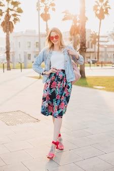 Całkiem uśmiechnięta kobieta spacerująca ulicą miasta w stylowej drukowanej spódnicy i dżinsowej kurtce oversize w różowych okularach przeciwsłonecznych