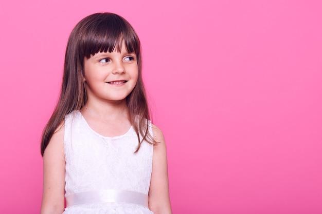 Całkiem uśmiechnięta mała dziewczynka o ciemnych włosach, odwracająca wzrok ze szczęśliwym wyrazem twarzy, ubrana w białą sukienkę, kopia miejsce na promocję, odizolowane na różowej ścianie