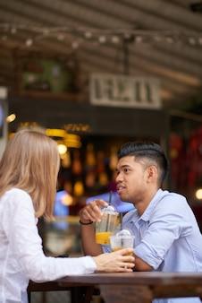 Całkiem uśmiechnięta młoda kobieta delektująca się orzeźwiającym napojem i rozmowa z chłopakiem