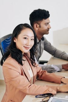 Całkiem uśmiechnięta młoda kobieta siedzi przy biurku obok swojego kolegi i pracuje na laptopie